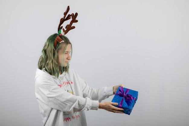 Portrait d'une jeune femme modèle offrant un cadeau.