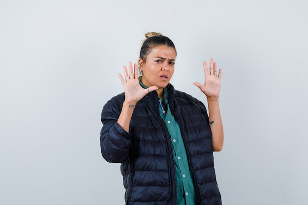 Portrait de jeune femme montrant un geste d'abandon en chemise, doudoune et à la vue de face effrayée