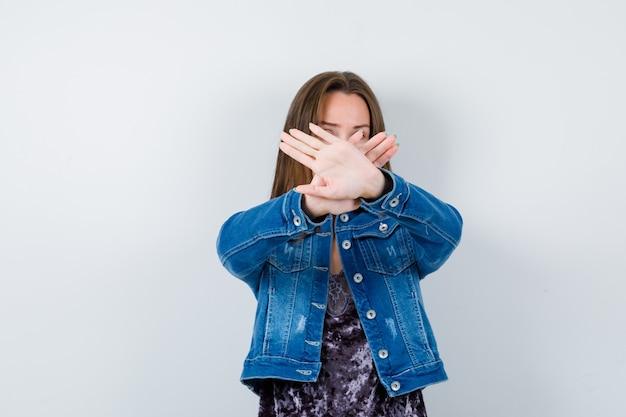 Portrait de jeune femme montrant un geste d'arrêt en blouse, veste en jean et à la vue de face sérieuse