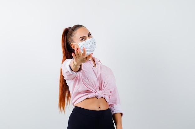 Portrait de jeune femme montrant le geste d'arrêt en chemise, pantalon, masque et à la vue de face ennuyée