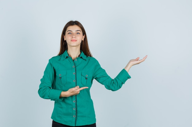 Portrait de jeune femme montrant un geste de bienvenue tout en pointant de côté en chemise verte et à la vue de face joyeuse