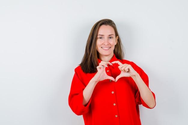 Portrait de jeune femme montrant le geste du coeur en blouse rouge et à la vue de face joviale