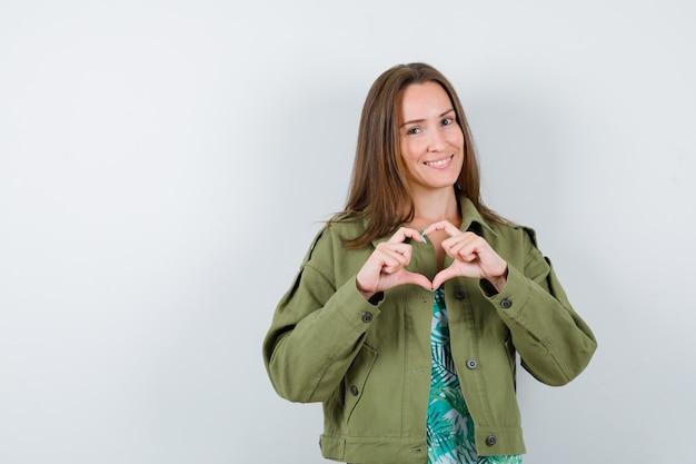 Portrait de jeune femme montrant le geste du coeur en blouse, veste et vue de face mignonne