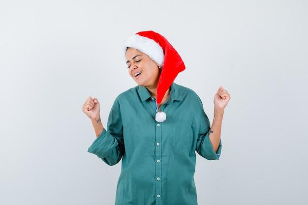 Portrait de jeune femme montrant le geste du gagnant en chemise, bonnet de noel et à la vue de face ravie