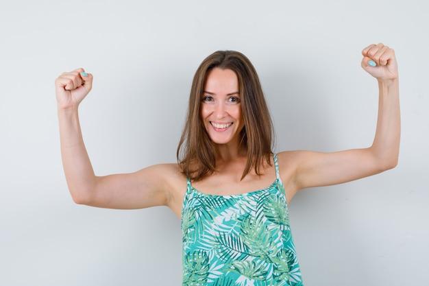 Portrait de jeune femme montrant le geste du gagnant et à la vue de face chanceux