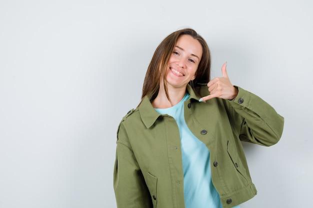 Portrait de jeune femme montrant le geste du téléphone en t-shirt, veste et regardant jolly front view