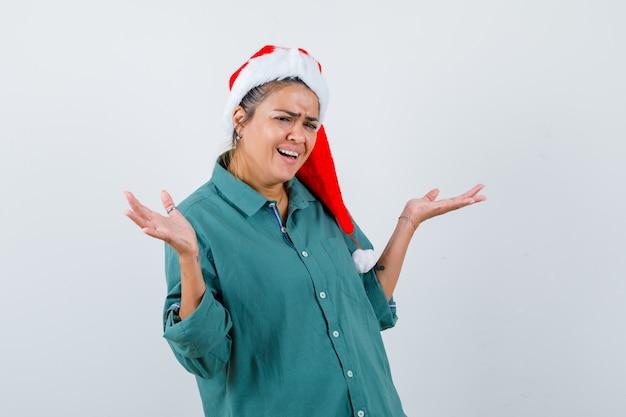 Portrait de jeune femme montrant un geste impuissant en chemise, bonnet de noel et à la vue de face impuissante