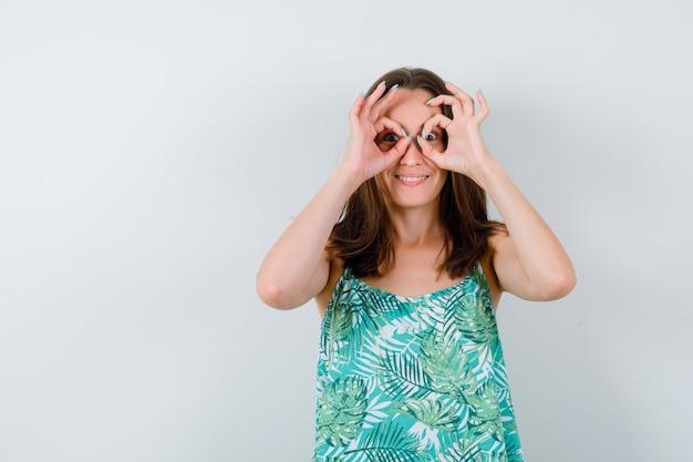 Portrait de jeune femme montrant un geste de lunettes en blouse et regardant une drôle de vue de face