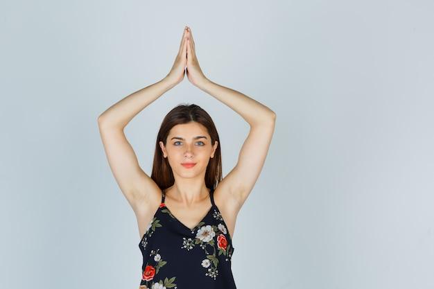 Portrait de jeune femme montrant le geste de namaste en blouse et à la vue de face pleine d'espoir