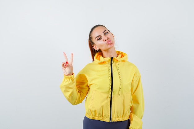 Portrait d'une jeune femme montrant un geste de paix, faisant la moue des lèvres en survêtement et semblant confiante en vue de face