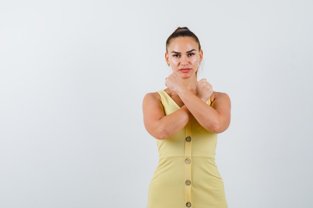 Portrait de jeune femme montrant un geste de protestation en robe jaune et à la vue de face sérieuse