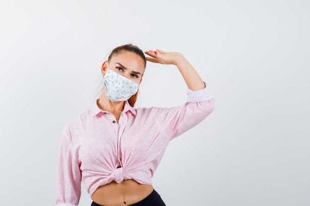 Portrait de jeune femme montrant le geste de salut en chemise, pantalon, masque et à la fière vue de face