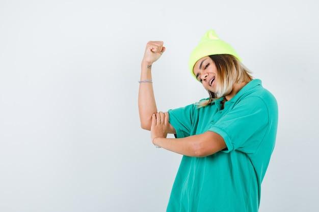 Portrait de jeune femme montrant les muscles des bras en t-shirt polo, bonnet et à la vue de face joyeuse