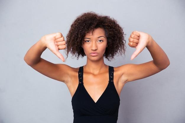 Portrait d'une jeune femme montrant le pouce vers le bas sur un mur gris
