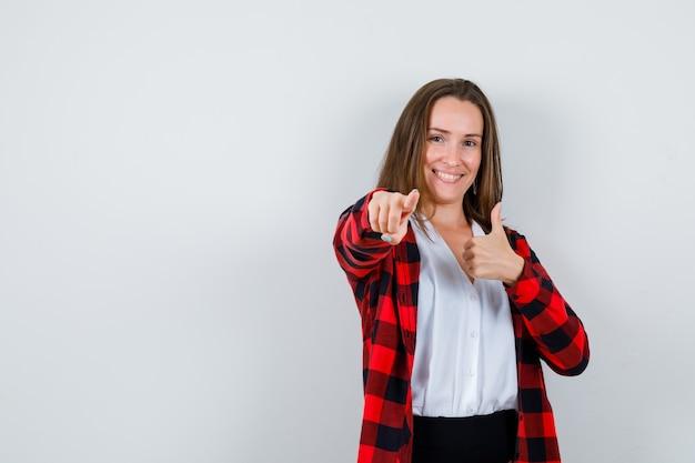 Portrait de jeune femme montrant le pouce vers le haut, pointant vers l'avant dans des vêtements décontractés et regardant joyeuse vue de face