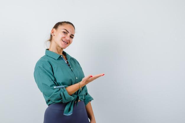 Portrait De Jeune Femme Montrant Quelque Chose Dans L'espace De Copie. Chemise Verte Et Vue De Face Gaie Photo Premium