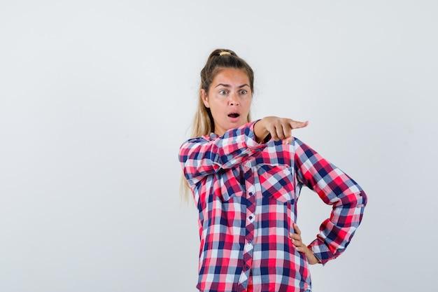 Portrait de jeune femme montrant quelque chose de loin en chemise à carreaux et à la vue de face surprise