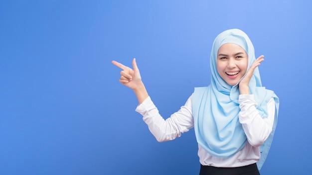 Portrait d'une jeune femme musulmane avec hijab sur bleu