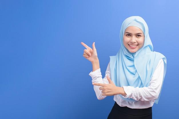 Portrait d'une jeune femme musulmane avec hijab sur fond bleu studio.