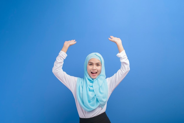 Portrait d'une jeune femme musulmane avec hijab sur mur bleu