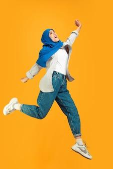 Portrait de jeune femme musulmane sur jaune