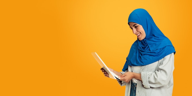 Portrait de jeune femme musulmane sur mur jaune