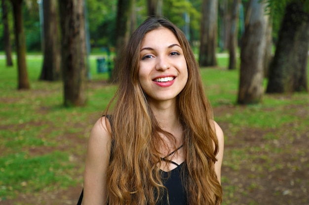 Portrait de jeune femme naturelle dans le parc avec des arbres en arrière-plan