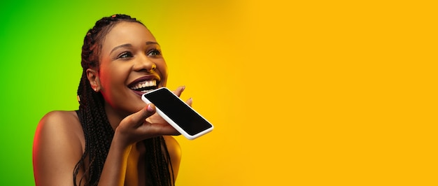 Portrait de jeune femme en néon sur fond dégradé. parler au téléphone.