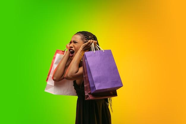 Portrait de jeune femme en néon avec des sacs à provisions