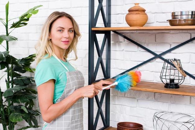 Portrait d'une jeune femme nettoyante nettoyant des étagères avec un plumeau