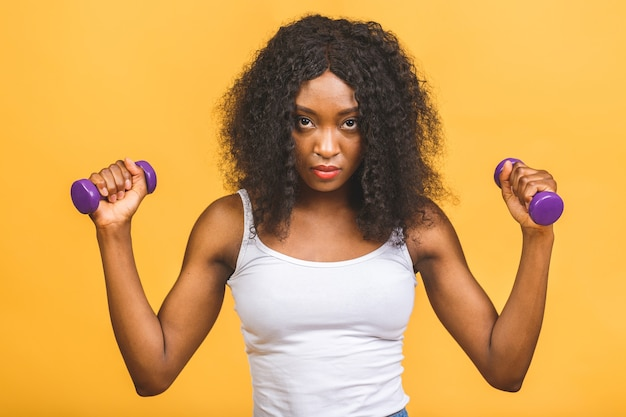 Portrait de jeune femme noire afro-américaine exerçant son muscle avec des haltères