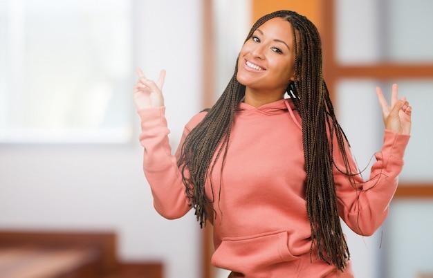 Portrait d'une jeune femme noire portant des tresses amusantes et gaies, positives et naturelles