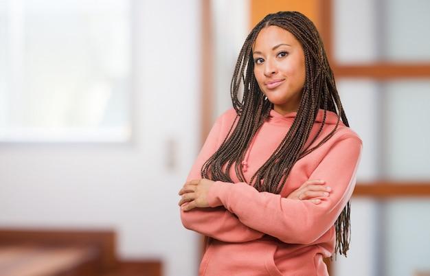 Portrait d'une jeune femme noire portant des tresses croisant les bras, souriante et heureuse, confiante et amicale