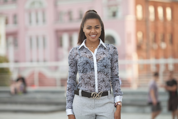 Portrait de jeune femme noire souriante debout à l'extérieur.