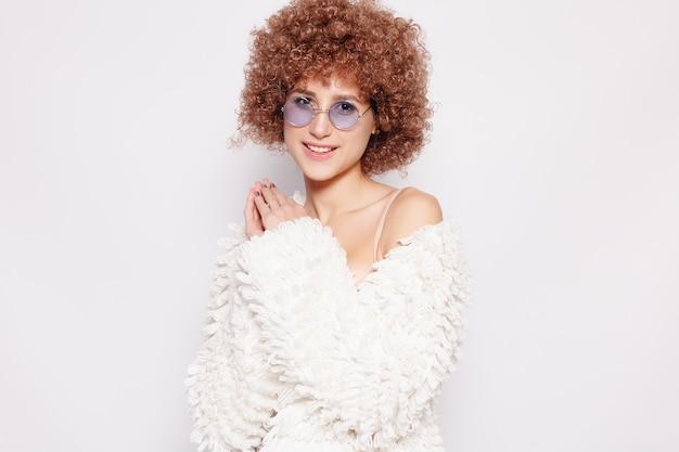Portrait de jeune femme noire souriante. portrait d'une belle jeune femme avec une coupe de cheveux afro-américaine et un maquillage glamour. prise de vue en studio. jolie fille portant des lunettes.