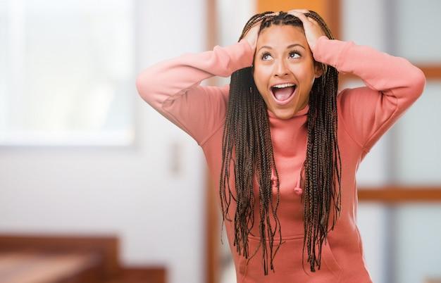 Portrait d'une jeune femme noire vêtue de tresses frustrée et désespérée