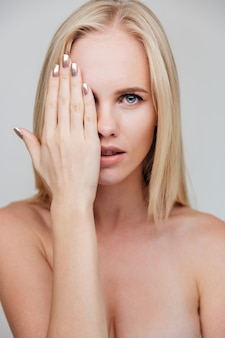Portrait d'une jeune femme nue couvrant son œil avec palm isolated