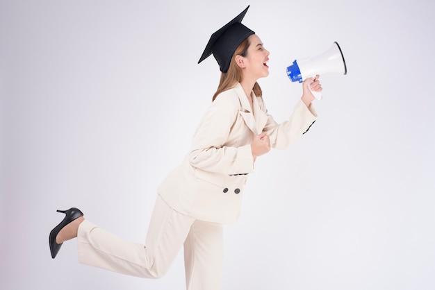 Portrait de jeune femme a obtenu son diplôme sur fond blanc