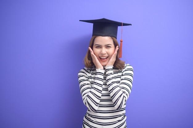 Un portrait de jeune femme a obtenu son diplôme sur fond bleu
