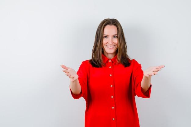 Portrait de jeune femme ouvrant les bras pour un câlin en blouse rouge et regardant joyeuse vue de face