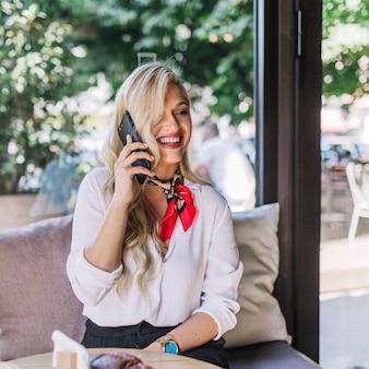 Portrait d'une jeune femme parlant au téléphone intelligent dans le café