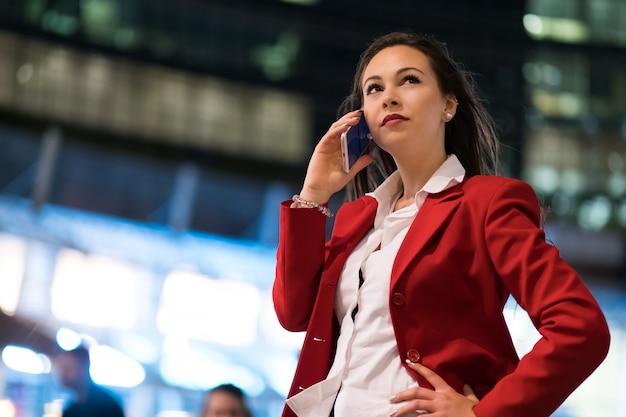 Portrait d'une jeune femme parlant au téléphone en plein air dans la ville en fin de soirée