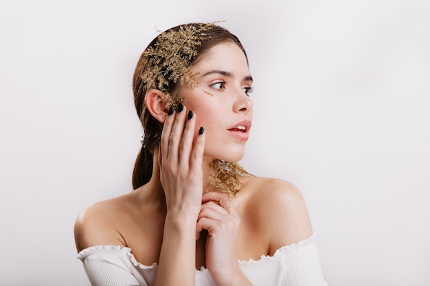 Portrait de jeune femme à la peau parfaite, posant avec de belles feuilles dans les cheveux noirs sur un mur isolé.