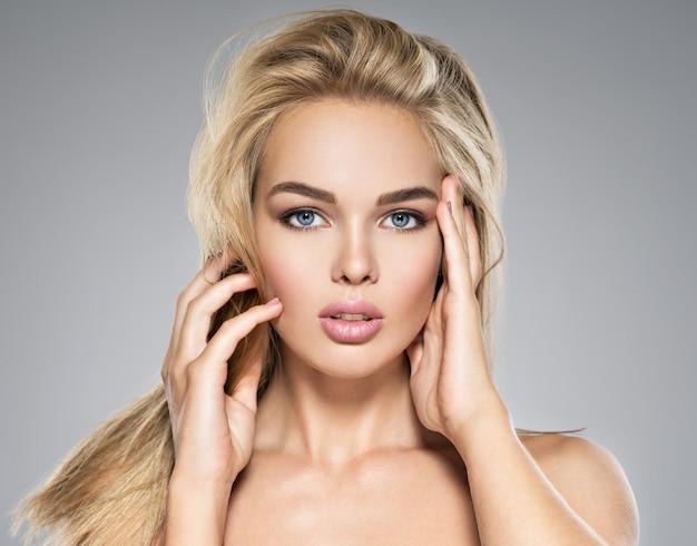 Portrait de jeune femme avec une peau saine d'un visage. jolie femme avec de longs poils raides et un maquillage brun. jolie fille magnifique aux yeux bleus - posant