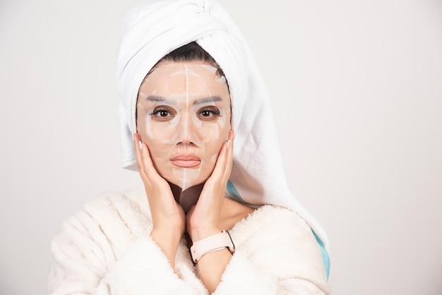 Portrait de jeune femme en peignoir et serviette sur la tête tout en touchant son visage avec masque facial
