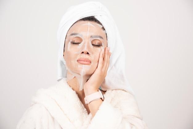 Portrait de jeune femme en peignoir et serviette sur la tête tout en touchant son visage avec un masque.