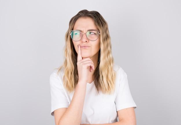 Portrait de jeune femme pensant avec son doigt sur sa tête et regarde sur le côté