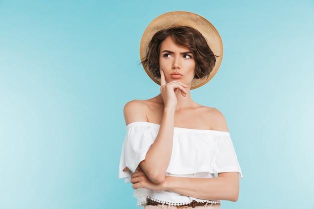 Portrait d'une jeune femme pensive au chapeau d'été