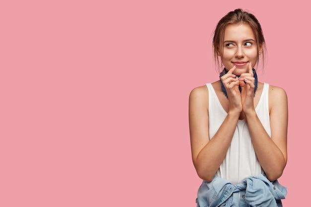 Portrait de jeune femme pensive avec des lunettes posant contre le mur rose