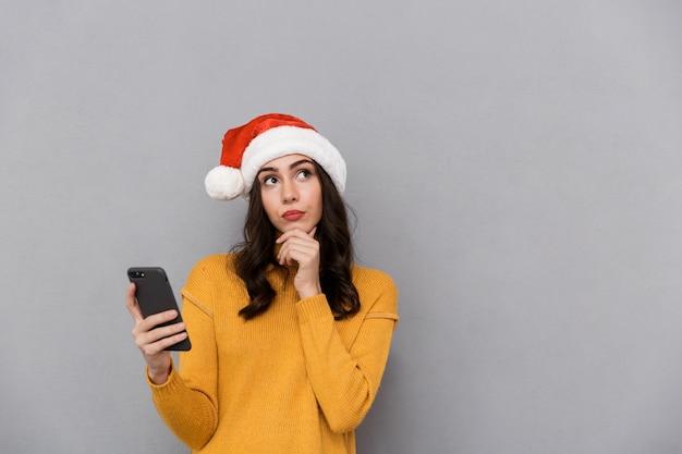 Portrait d'une jeune femme pensive portant chapeau de père noël rouge isolé sur fond gris, à l'aide de téléphone mobile